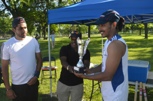 York University captain Arul Raja (right) smiles as he holds the CIMA University Cricket championship trophy. Looking on is Hassan Jamil (left), who won the Best Batsman award.